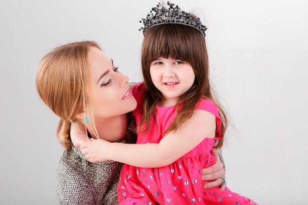왕관과 회색 배경에 포옹하는 아름 다운 어머니와 핑크 공주 드레스에 아름 다운 작은 소녀.