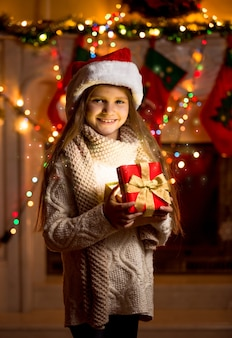 반짝이 선물 상자를 들고 빨간 모자에 아름 다운 소녀