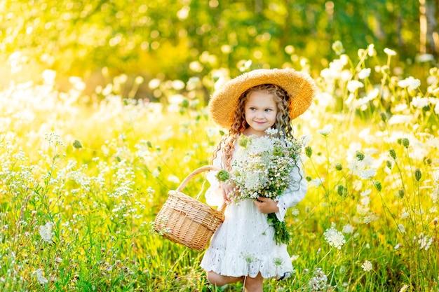 ターンテーブルの上を吹く花と黄色のフィールドにサングラスで美しい少女