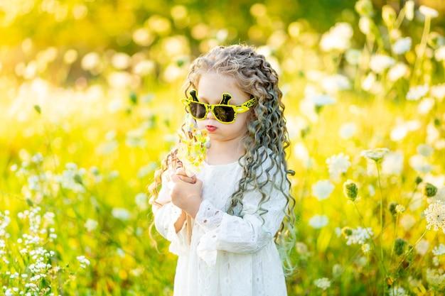 Красивая маленькая девочка в солнцезащитных очках летом в желтом поле с цветами, дующими на поворотный стол.