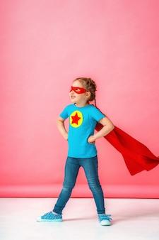 Красивая маленькая девочка в костюме супергероя в красном плаще и маске показывает, насколько сильна