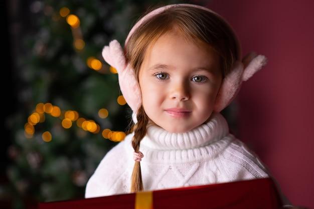 선물 및 크리스마스 트리 bokeh 조명 근처에 앉아 모자에서 아름 다운 소녀