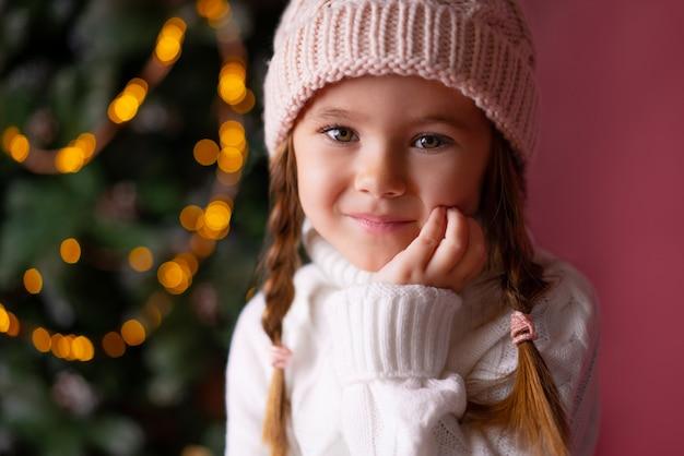 プレゼントやクリスマスツリーのそばに座って帽子の美しい少女