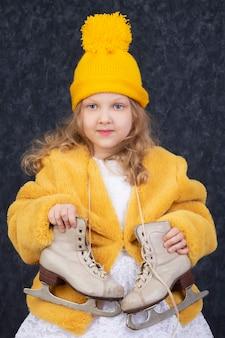 Красивая маленькая девочка в зимней одежде с белыми коньками. пятилетний ребенок в вязаной желтой шапочке.