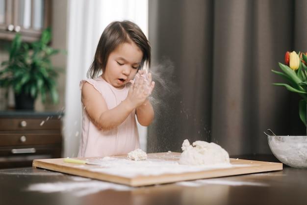 아름다운 소녀가 밀가루로 손뼉을 치고 있다 아이가 부엌에서 밀가루를 가지고 놀고 있다