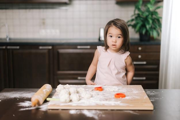 아름다운 소녀가 쿠키 형태로 반죽을 자르고 있다