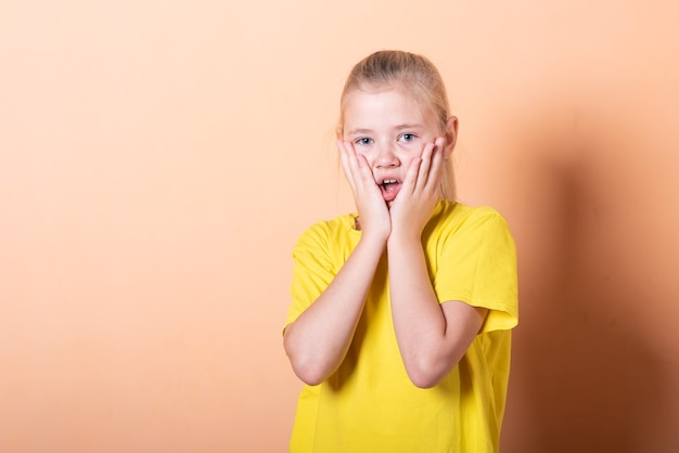 Beautiful little girl is embarrassed on a light orange background. for any purpose.