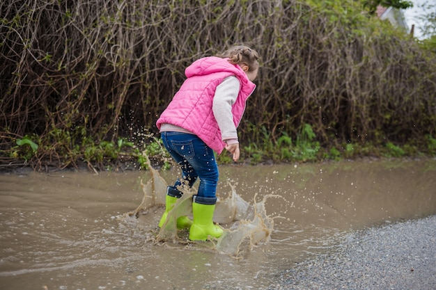 A beautiful little girl is walking down the street and in green rubber boots through puddles. shooting from the back. a girl walks down the street and jumps in puddles.