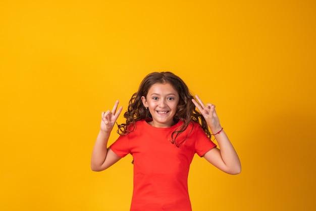 Красивая маленькая девочка прыгает на желтом фоне с пространством для текста.
