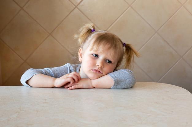 テーブルのそばに座って美しい少女子供悲しいまたは退屈