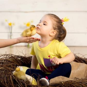 美しい少女はかわいいふわふわイースターアヒルの子にキスします。