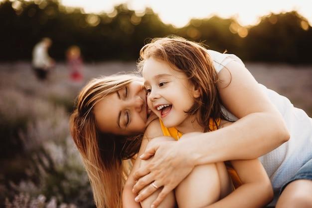 일몰에 대 한 꽃의 분야에서 야외 그녀의 젊은 어머니에 의해 수용되는 동안 웃 고 아름 다운 작은 소녀.