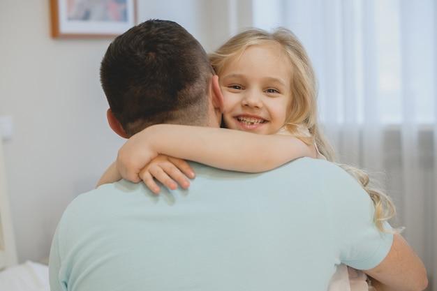 Красивая маленькая девочка смеется, обнимая своего отца дома утром.