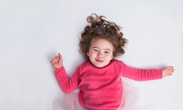 Beautiful little girl lies on the white floor and smile. the concept of a happy childhood.
