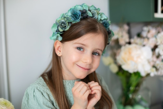 Beautiful little girl looking in camera with gentle smile making heart gesture with hands