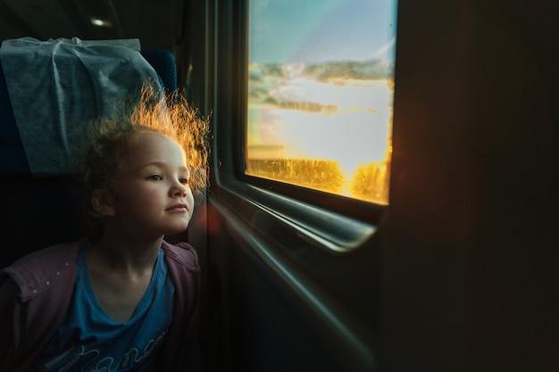 Beautiful little girl looking out train window outside