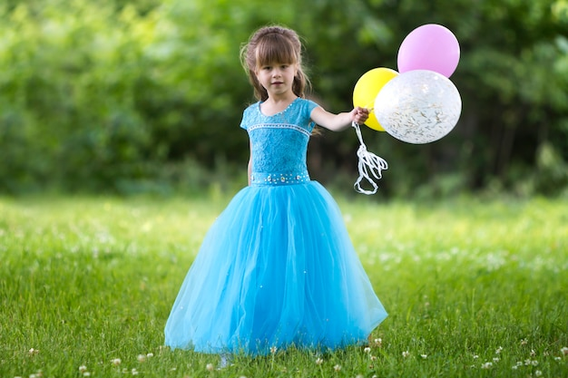 Beautiful little girl in nice long blue evening dress looking like princess looks  holding colorful balloons