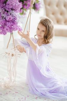ライラックの花で飾られたブランコに座っている繊細なドレスを着た就学前の美しい少女