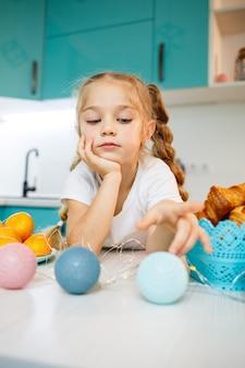7歳の美しい少女。台所のテーブルに座っています。白いtシャツを着ています。子供の顔の幸せと喜び