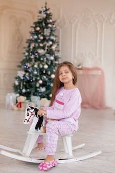 A beautiful little girl in pink pajamas rejoices in a wooden rocking horse, a gift from santa for christmas.