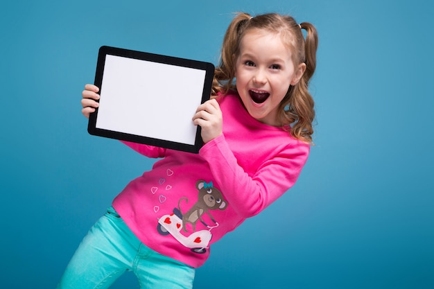 Beautiful little girl in pink shirt and blue trousers holding empty tablet