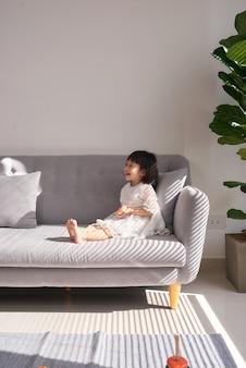 ソファで遊ぶ美しい少女