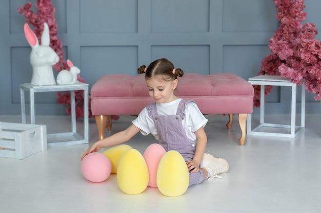Красивая маленькая девочка играет с разноцветными пасхальными яйцами маленький фермер охотится на пасхальные яйца