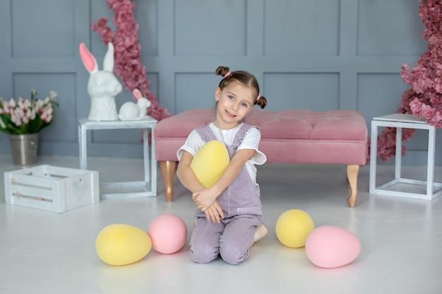 Красивая маленькая девочка играет с разноцветными игрушечными яйцами, собирая пасхальные яйца на охоте на маленького фермера