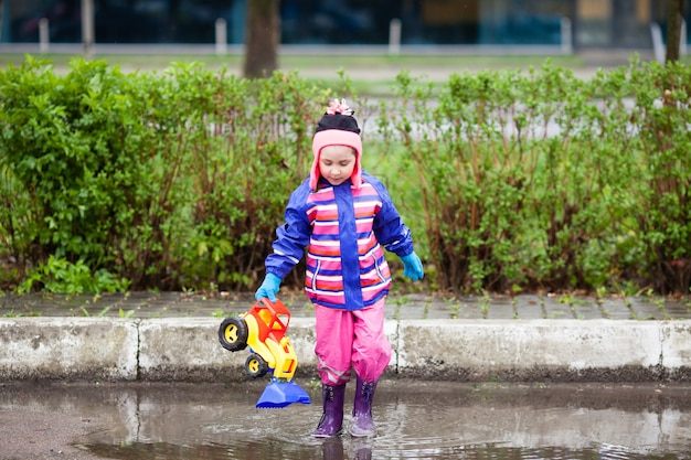 Beautiful little girl playing with a tractor in the puddle