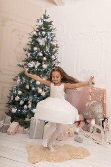 Beautiful little girl posing near the christmas tree.