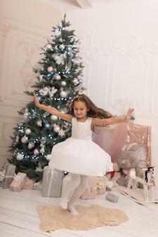Красивая маленькая девочка позирует возле елки.