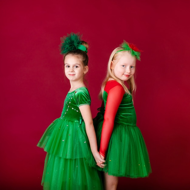 Beautiful little girl princesses dancing in luxury green dress isolated on red wall. carnival party with costumes