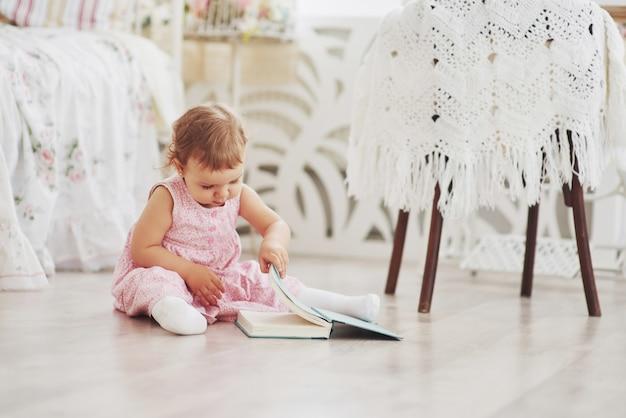 Красивая маленькая девочка читает книгу со своим любимым мишкой на мягком плюшевом одеяле