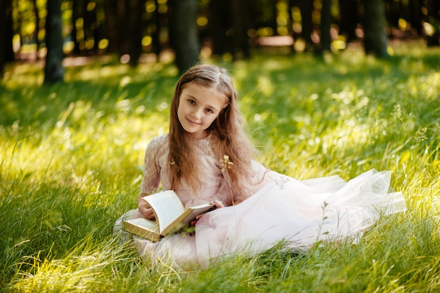 A beautiful little girl reads a book in the park.