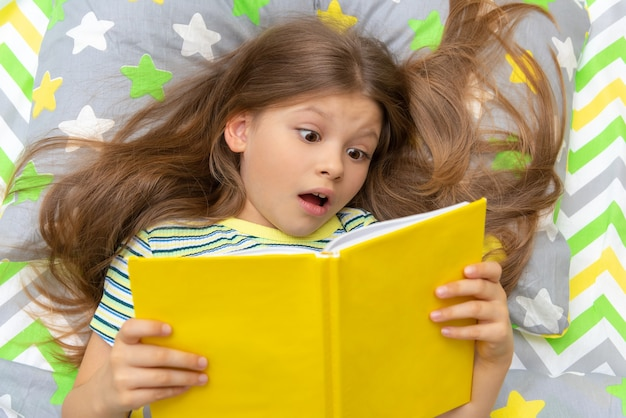 A beautiful little girl reads an interesting fairy tale in bed before going to bed.