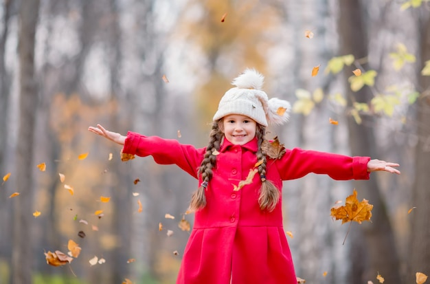 Beautiful little girl in red coat with autumn leaves outdoors in a park.