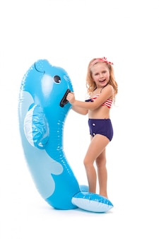 Beautiful little girl in in red striped bikini, blue bottoms and red wreath stand bear the inflatable seal