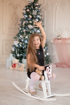Красивая маленькая девочка радуется деревянной лошадке-качалке, рождественскому подарку от санты.
