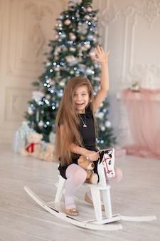 Красивая маленькая девочка радуется деревянной лошадке-качалке