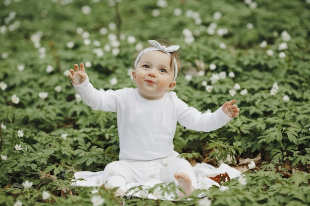 Beautiful little girl rejoices in the forest among the flowers
