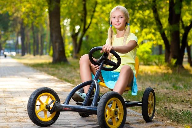 夏の都市公園で美しい少女乗馬おもちゃの車