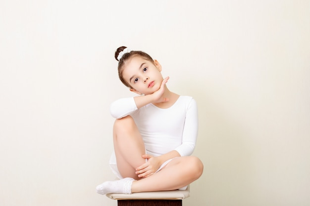 Beautiful little girl sits beautifully in a white dance swimsuit