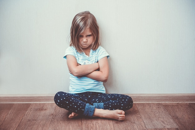 Beautiful little girl sitting on the floor, toned image. disappointment, sadness, melancholy concept