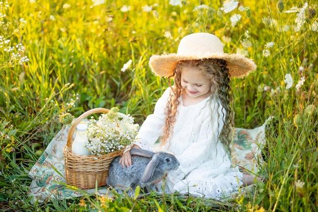 ウサギとカモミールフィールドで麦わら帽子に座っている美しい少女