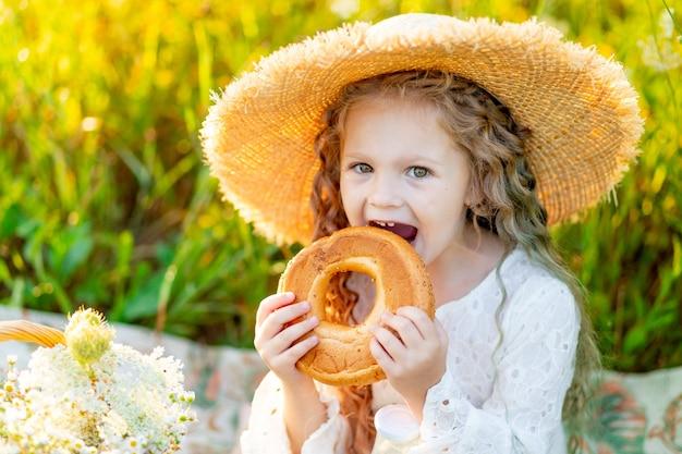 Красивая маленькая девочка сидит в соломенной шляпе в поле и ест рогалик
