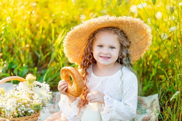 Красивая маленькая девочка сидит в соломенной шляпе в желтом поле с полевыми цветами с бутылкой молока и бубликом