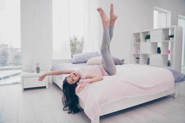 Красивая маленькая девочка, сидящая на своей кровати в спальне