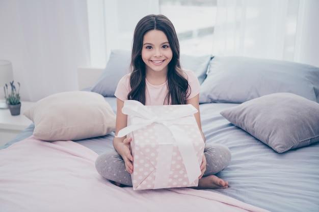 큰 선물 상자와 함께 그녀의 침대에 앉아 아름 다운 작은 소녀
