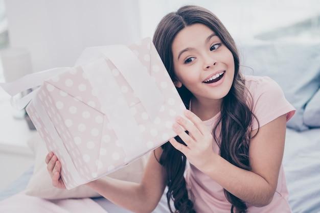 Красивая маленькая девочка сидит на своей кровати с большой подарочной коробкой