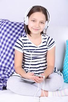 Красивая маленькая девочка сидит на диване и слушает музыку на фоне домашнего интерьера